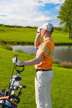 Male golfer looking into a rangefinder at his hit