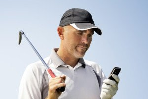 A male golfer using his mobile phone.