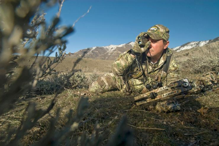 Hunter in camouflage using camouflage rangefinder